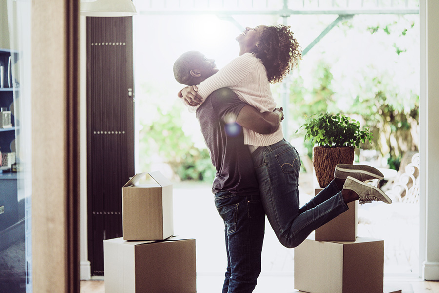 A photo of happy man lifting woman in new house. Side view of loving and excited couple are in casuals. They are with cardboard boxes at entrance.
