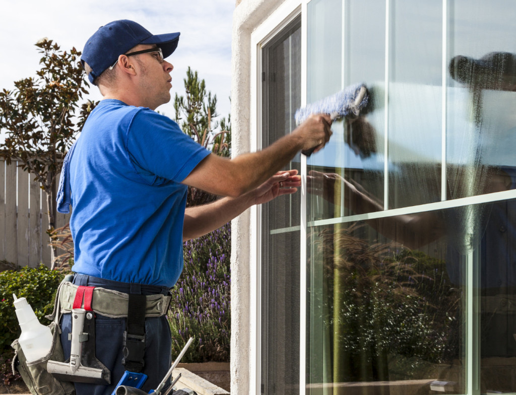 Man cleaning window of a home.